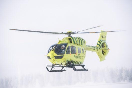 Lääkärihelikopteri lentää talvisessa säässä.